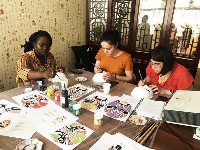 Homestay tutors painting Peking opera masks in Beijing